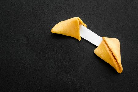 Fortune cookie cracked with blank slip on black background copy space 版權商用圖片