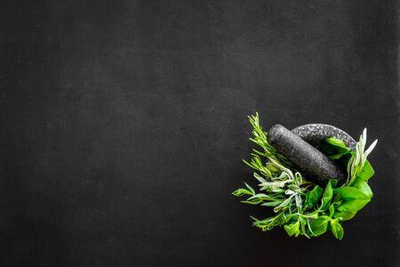 Herbs in ceramic mortar with pestle on black backgroud top-down.