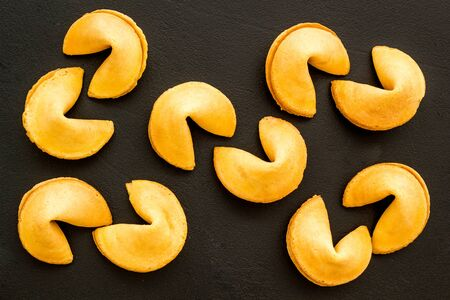 Fortune cookie background on black table top-down pattern Archivio Fotografico