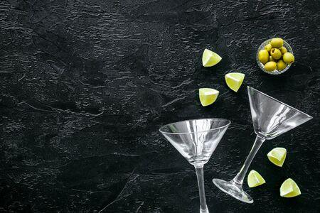 Aperitif drink concept. Martini glasses near olives and lemon on black background.