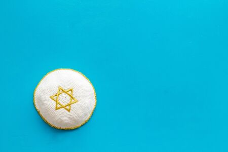 Jewish Kippah Yarmulkes hats with Star of David on blue table. Religion Judaisim symbol. Top view, space for text. Stock Photo