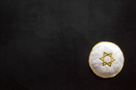 Jewish Kippah Yarmulkes hats with Star of David on black table. Religion Judaisim symbol. Top view, space for text.