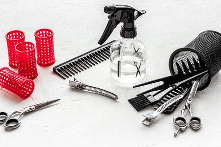 Hairdresser desk with combs, scicoors, spray and curlers on white background.