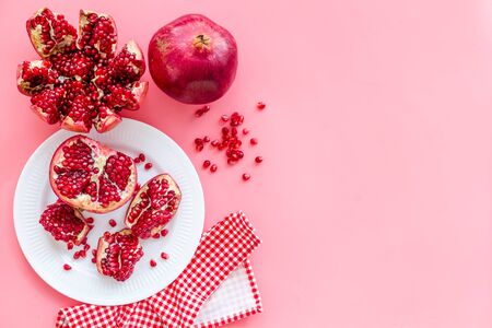 Juicy pomegranate with seeds on plate on pink table top-down copy space