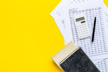 Financial literature. Books near documents, calculator on yellow background top-down.
