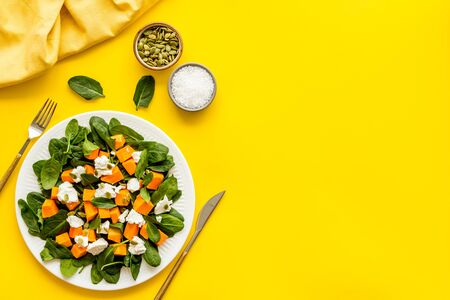 Vegeterian meal concept. Salad with pumpkin and basil on yellow background top-down.