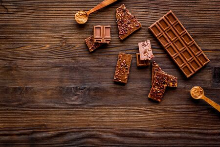 Homemade chocolate. Bars and broken pieces on wooden table.