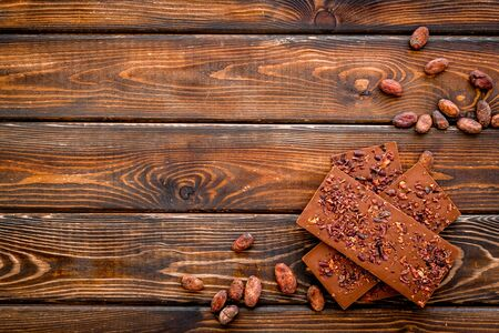 Chocolate - stack of dark bars - on dark wooden background top-down copy space