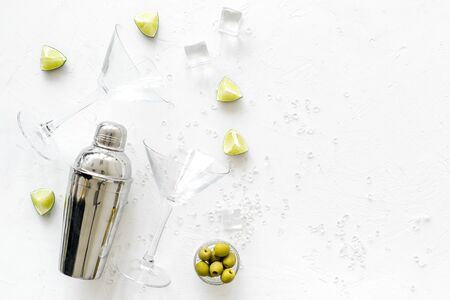 Cocktail concept. Martini glasses and shaker - near lemon, olives, ice - on white background top-down copy space 版權商用圖片