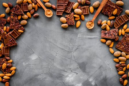 Sweets frame. Broken chocolate slices and nuts on grey stone background top-down copy space 版權商用圖片