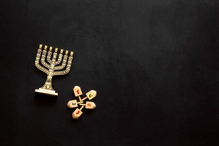 Jewish holiday Hanukkah with menorah - traditional Candelabra - and wooden dreidels spinning top. Black background, top view, copy space