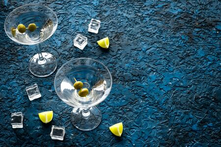 Martini with olives and ice on blue background copy space