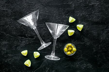 Aperitif drink concept. Martini glasses near olives and lemon on black background copy space 版權商用圖片