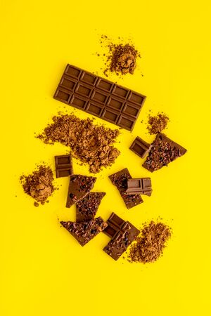 Chocolate frame. Broken bars and cocoa powder on yellow background.