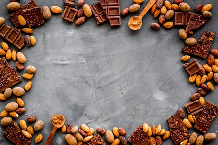 Sweets frame. Broken chocolate slices and nuts on grey stone background top-down.