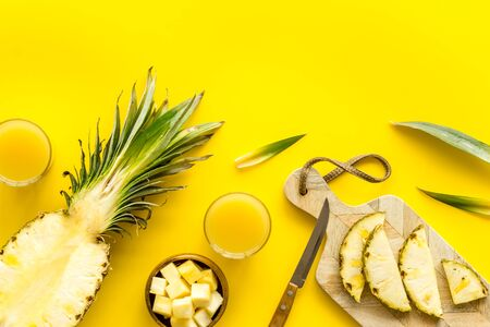 Make pineapple juice. Glasses near sliced fruits on yellow background top-down.