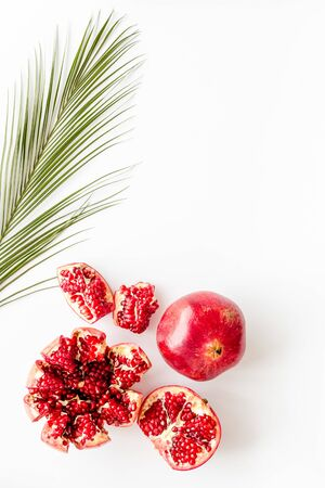 Ripe pomegranate fruit near leaf on white background top-down copy space