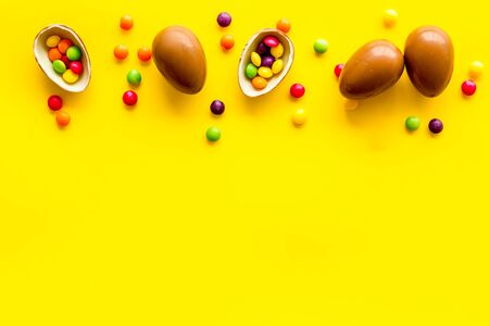Chocolate eggs - Easter symbol - frame on yellow background top-down.