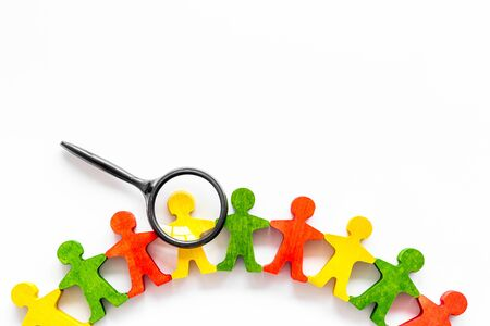 Wooden figures of people under black magnifying glass on white background. Recruitment, hiring, leadership concept. Top view.
