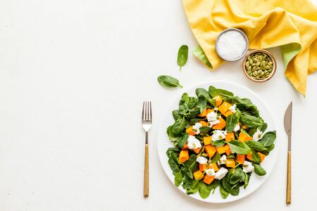 Vegeterian meal concept. Salad with pumpkin and basil on white background top-down.