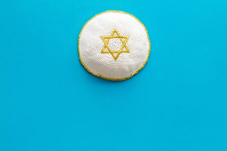 Jewish Kippah Yarmulkes hats with Star of David on blue table. Religion Judaisim symbol. Top view, space for text