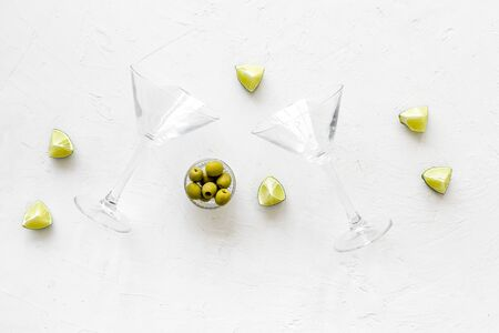Aperitif drink concept. Martini glasses near olives and lemon on white background