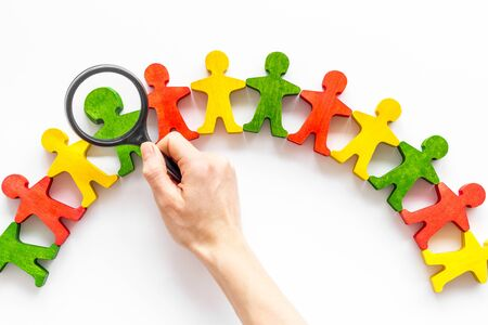 Wooden figures of people under black magnifying glass on white background. Recruitment, hiring, leadership concept.