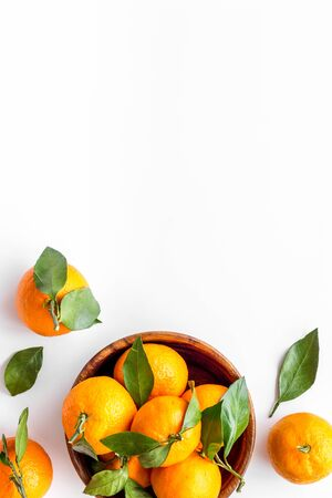 Ripe tangerines on white table. Citruses with green leaves in bowl top-down copy space
