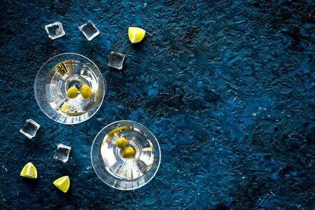 Aperitif drink concept. Martini glasses near olives and lemon on blue background copy space Stockfoto