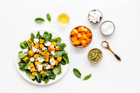 Salad with pumpkin and basil - near ingredients - on white background top-dow