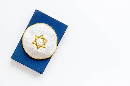 Jewish Kippah Yarmulkes hats with Star of David on Prayer book. Religion Judaisim symbols on white table. Top view, space for text