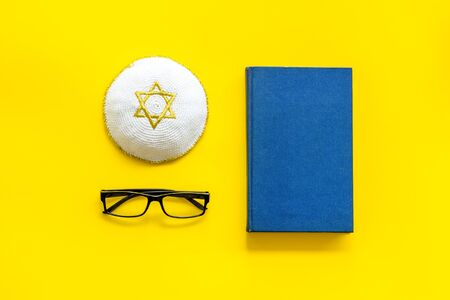 Jewish Kippah Yarmulkes hats with Star of David with Prayer book. Religion Judaisim symbols on yellow table. Top view, space for text