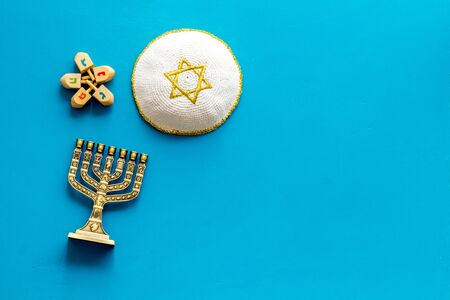 Jewish Kippah Yarmulkes hats with Star of David with menorah. Religion Judaisim symbols on blue table. Top view, space for text Stock Photo