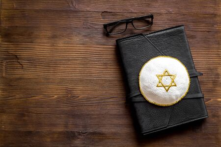 Jewish Kippah Yarmulkes hats with Star of David on Prayer book. Religion Judaisim symbols on wooden table. Top view, space for text.