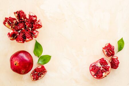 Ripe pomegranate fruit near leaf on beige background top-down.