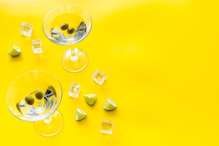 Martini with olives and ice on yellow background.