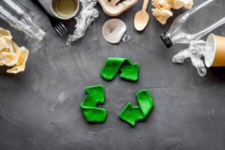 Recycle concept. Green arrows icon among waste on grey background top-down