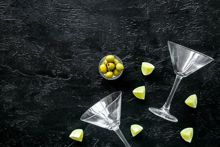 Aperitif drink concept. Martini glasses near olives and lemon on black background copy space Stockfoto