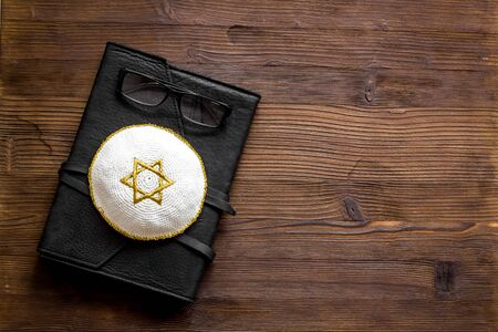 Jewish Kippah Yarmulkes hats with Star of David on Prayer book. Religion Judaisim symbols on wooden table. Top view, space for text