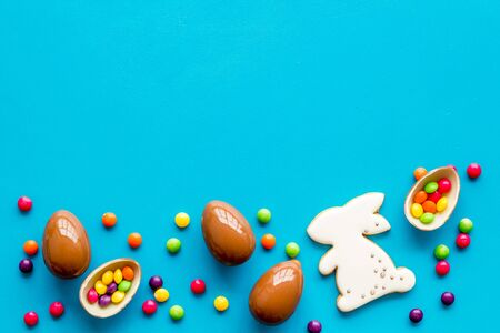 Sweet Easter symbols - chocolate eggs and bunny gingerbread - on blue background top-down.