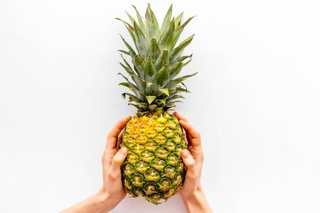 Pineapple in hands on white background top-down copy space