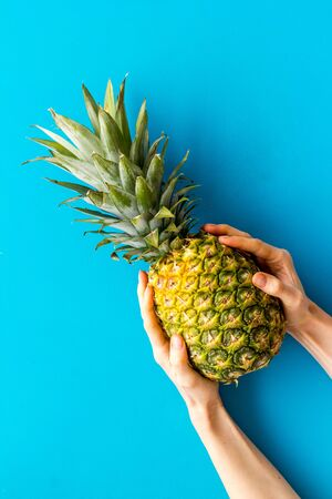 Pineapple in hands on blue background top-down.