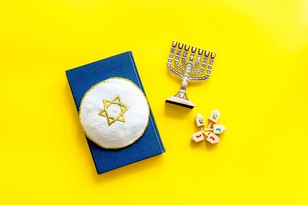 Jewish Kippah Yarmulkes hats with Star of David on Prayer book with menorah. Religion Judaisim symbols on yellow table. Top view, space for text.