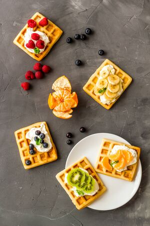 Belgian waffles with creamy cheese and berries on grey background top-down.