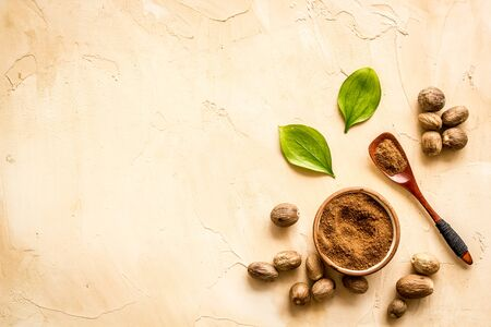 Nutmeg - ground indian condiment in spoon - on beige background top-down.