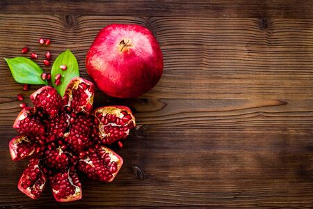 Ripe pomegranate fruit near leaf on dark wooden background top-down.