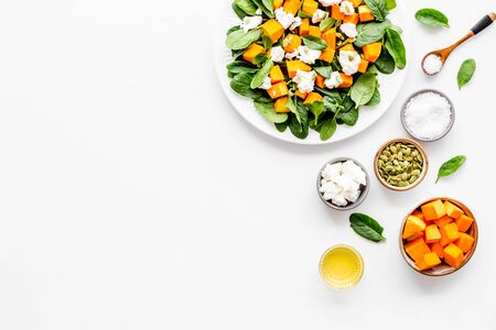 Salad with pumpkin and basil - near ingredients - on white background top-down.