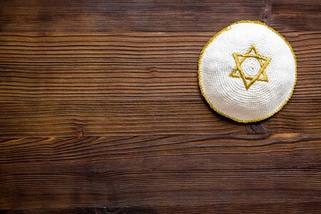 Jewish Kippah Yarmulkes hats with Star of David on wooden table. Religion Judaisim symbol. Top view, space for text.
