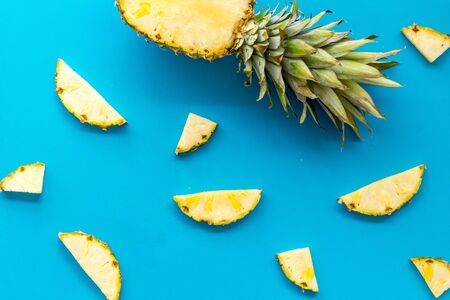 Pineapple - half of fruit and slices - on blue background top-down.