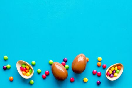 Chocolate eggs - Easter symbol - frame on blue background top-down.